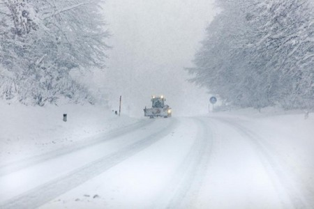 Plow on snow covered road in blizzard conditions